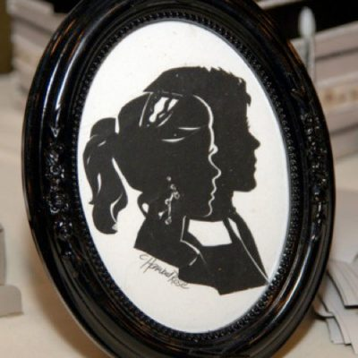 She offers the bride and groom lovely oval picture frames of their silhouettes facing one another, as a wedding gift from the premier silhouette artist.
